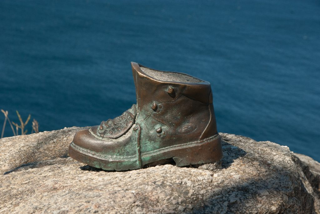 bronze hiking boot with ocean behind